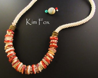 A necklace of red abalone, lampwork beads by Marcia Kmack, African Bronze, kumihimo and clasp and cones by Kim Fox 22 inches long