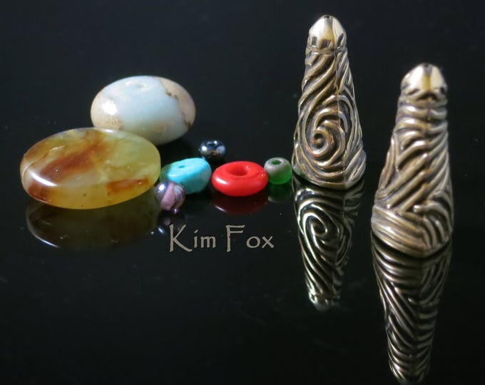 KF 345 A pair of Triangular Cones with Swirl Texture in Golden Bronze 24mm x 9 mm opening designed by Kim Fox