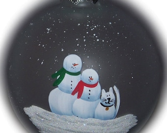 """Our family with a snow cat hand painted on a 3 1/4"""" frosted glass ornament."""