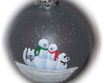 """Our family with a snow cat and snow dog hand painted on a 3 1/4"""" frosted glass ornament."""