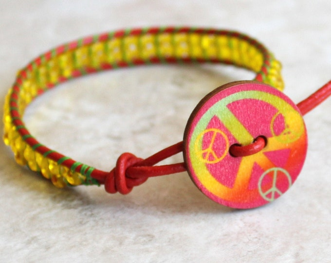 peace sign bracelet with red leather cord and yellow glass beads