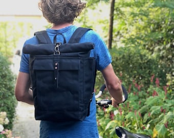 Waterproof black backpack with padded shoulder straps and water bottle pocket, unisex collection