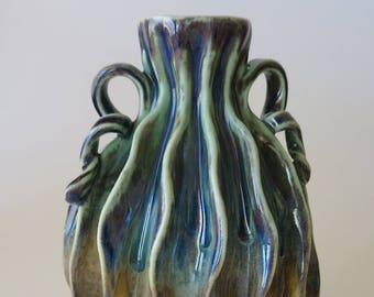 Carved porcelain vase in blue, green, purple, tan, caramel & white with grooves and handles
