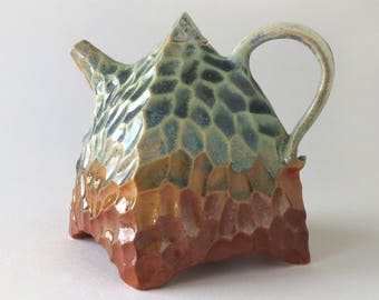 Teapot in carved porcelain, green, orange glaze, textured, small scale