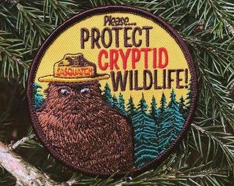 Cryptid PSA Patch - Cryptozoology Tracking Society Bigfoot Sasquatch Badge NPS Smokey the Bear Woodland Hiking Camping Fishing Hunting