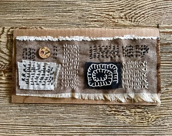Embroidered panel with wooden button