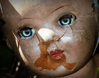 big blue eyes in a creepy doll head art photo, broken doll with luminous eyes, outsider art, spooky freaky wall decor