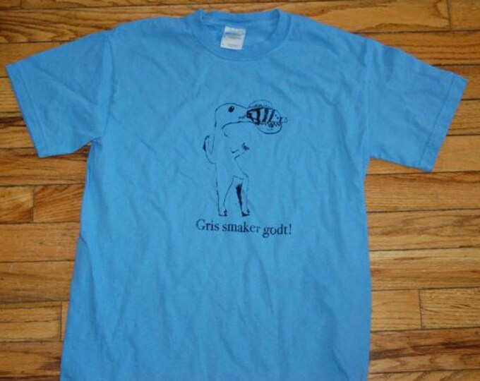 Gris smaker godt Norwegian shirt designed by Vera Pig is Tasty Adult Small Crocodile eating a pig Light Blue