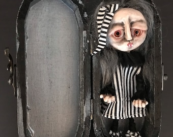 Art doll in wooden coffin, clay doll