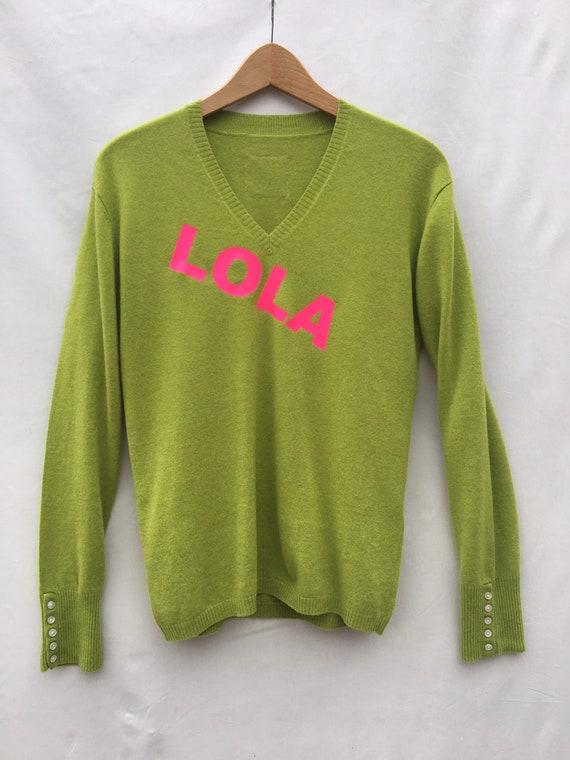 Maglia in cashmére verde con stampa LOLA in fucsia. Pullover scollo V in cachemire riciclato