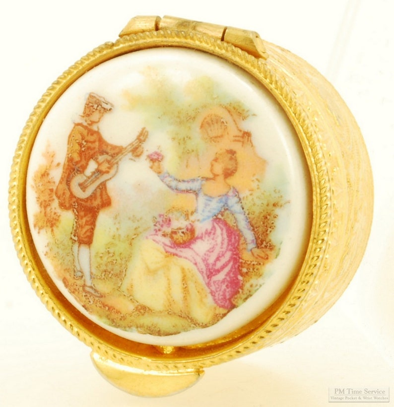 Gold-toned & porcelain pill box with image of a woman picking image 0