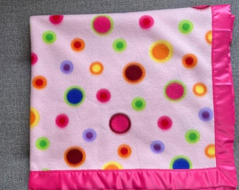 Fleece baby or toddler blanket in a pattern of multicolored circles and dots on a pale pink background, with pink satin trim
