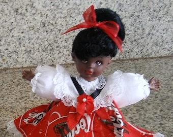 Black African American doll, with Coke Cola print dress