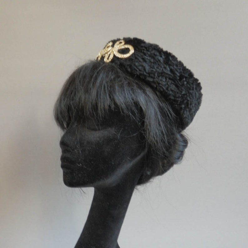 Jackie O pillbox hat in black astrakhan with goldish frog embellishment on comb