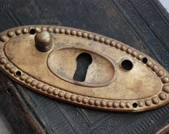 Vintage Art Nouveau style key hole escutcheon for drawer pull handles.