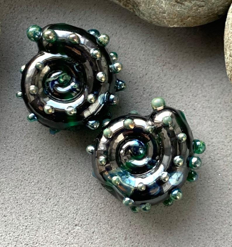 Deep green shiny metallic ammonite lampwork bead pair