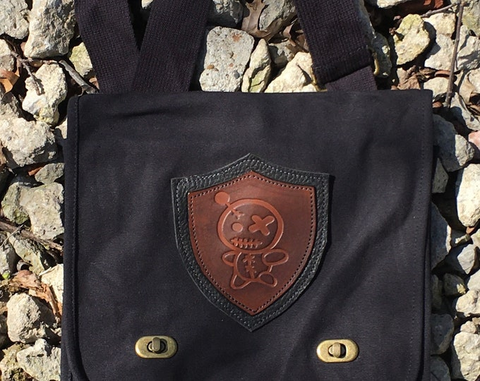 Canvas messenger bag with leather medallion voodoo doll