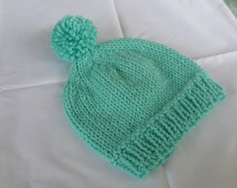 Child's hand knitted beanie hat with pompom in turquoise