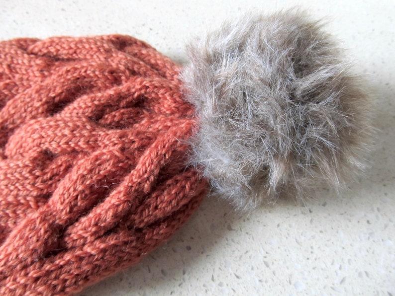 Cabled burnt orange wool beanie with tan pom pom