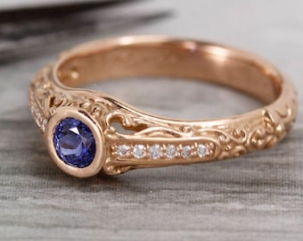 Filigree scroll ring with blue sapphire with diamonds.