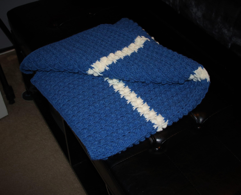 Couverture de bébé bleu de crochet avec la bande blanche