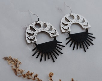 eclipse earrings in silver.  a pair of bohemian mixed metal moon phase and sun burst earrings