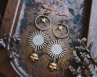 sol. a pair of mixed metal celestial boho silver and gold brass sun face star moon earrings