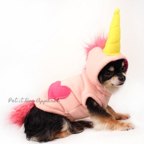 Small dog wearing pink fleece unicorn costume.