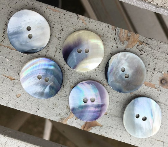 Pretty vintage mussel shell buttons with a pearly finish and lovely blue highlights