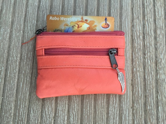 Genuine leather coin purse in CORAL pink-orange.Small leather pouche closed by zippers with metallic wing charm. Coin, bill and card holder