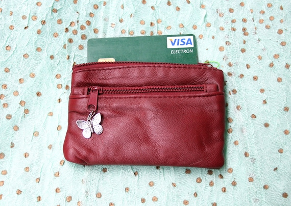 Small purse in wine red genuine leather. 3 Zippers, fits credit cards, coins, bills...Butterfly charm attached to one of the zippers.