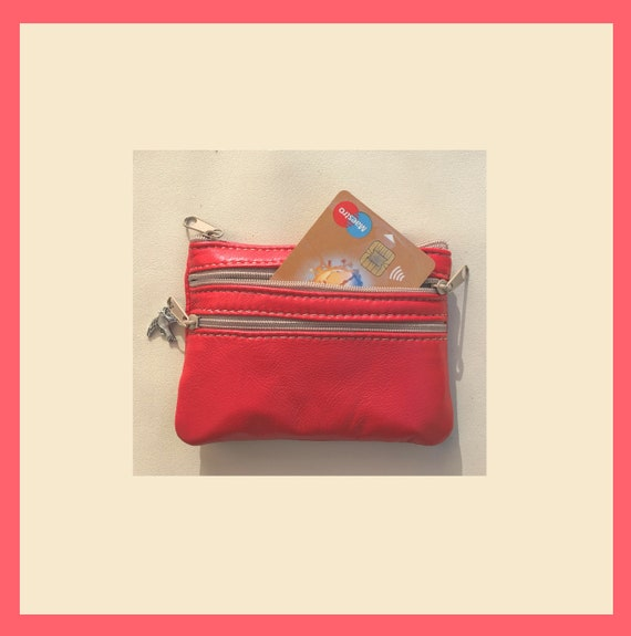 Red coin purse with zippers, genuine leather. Small wallet for credit cards, coins and notes. Soft red leather.