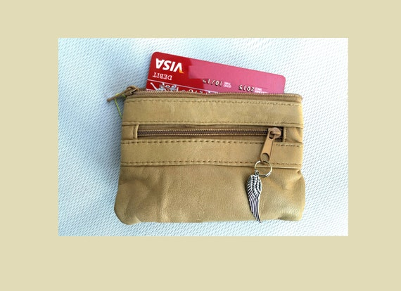 Genuine leather coin purse in BEIGE. Small leather wallet closed by zippers with metallic wing charm. Coin, bill and card holder
