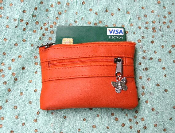 Small purse in orange genuine leather, closed by 3 zippers. Fits creditcards, coins, bills. Soft orange leather wallet.