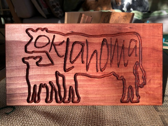 Cow-calf silhouette on stained wood