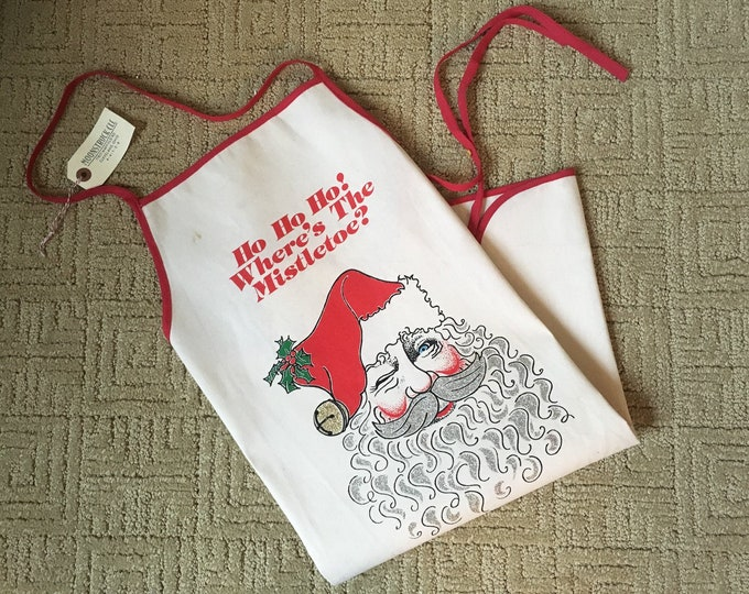 "Canvas Santa apron with glitter accents and ""ho ho ho where's the mistletoe?"" slogan 