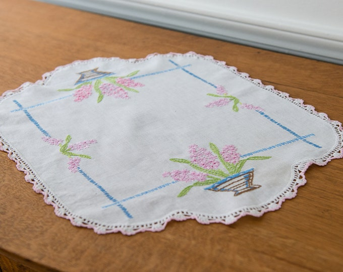 Vintage embroidered dresser scarf or doily with vase of pink flowers.