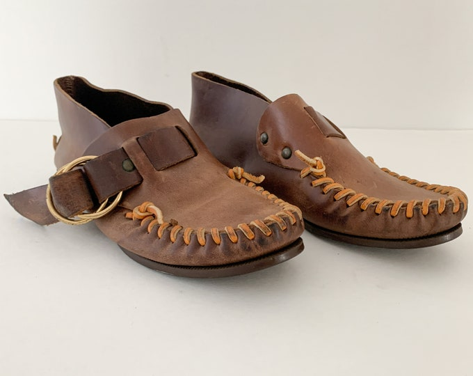 Vintage brown leather moccasins with brass buckles and rawhide whip stitching, made in Maine, Webster Rubber Company, Size 6