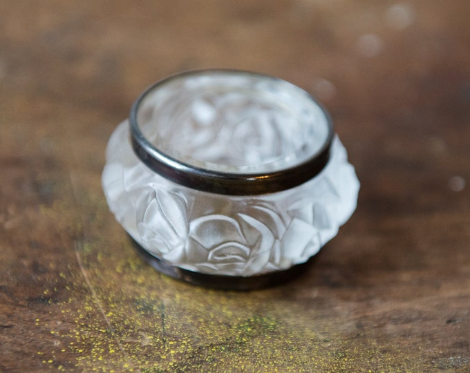 Vintage frosted glass napkin ring with raised floral rose pattern and silver plated trim