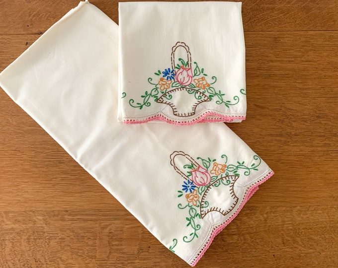 Pair of vintage cream colored hand-embroidered cotton pillowcases with flower basket design, standard size, farmhouse decor