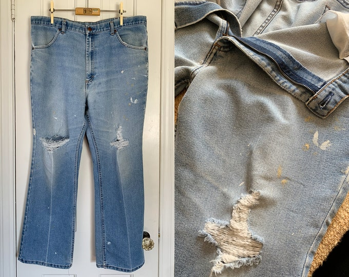 Vintage 1970s authenticlly distressed denim jeans with frayed knees and paint splatters | 36 x 27