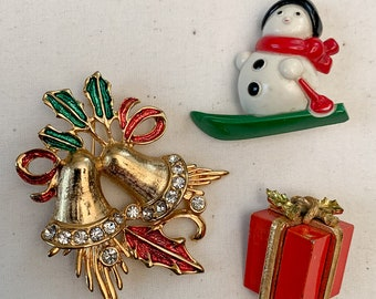 Vintage collection of 3 Christmas pins including rhinestone bells, a present and a snowman, Avon snowman pin, holiday lapel pins