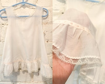 Vintage white cotton baby dress with ruffled hem and ribbon detail, baby doll dress