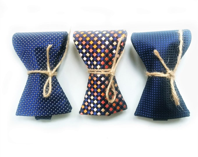 A wedding set of navy and orange textured silk self tie bow ties