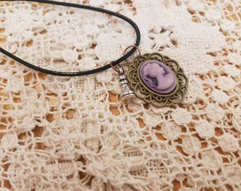 A Touch of Wonderland Purple filigree eged Cameo on black cord with silver rook necklace