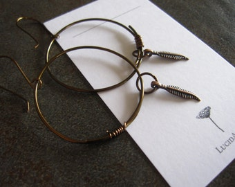 Antiqued bronze hammered hoop with copper feather charm earrings