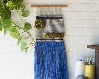 Woven Wall Hanging with Royal Blue Tassels and Green Inset Blocks on a Wood Dowel