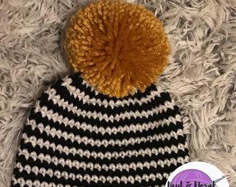 a4bbfe4cb7f Black   white striped hat with oversized gold pom pom