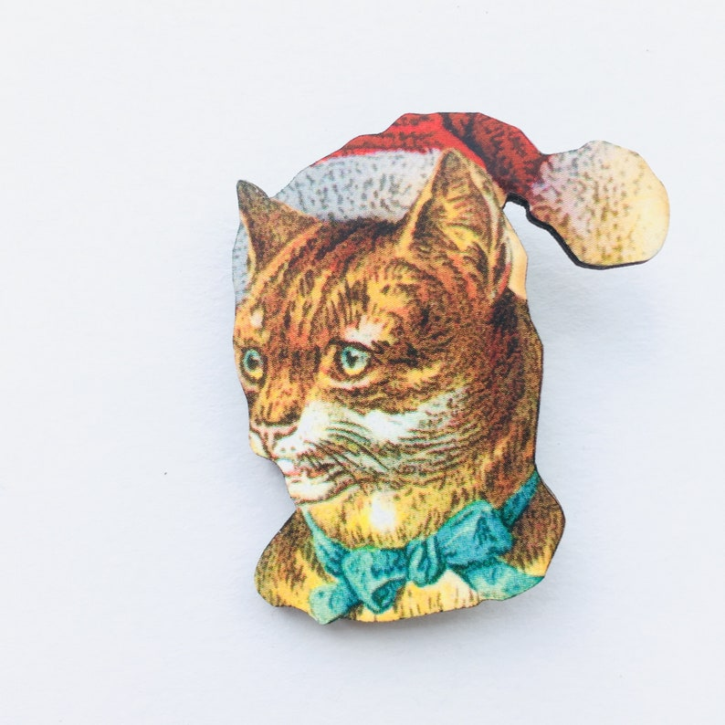 Tabby Cat with Santa Hat and Blue Ribbon  Portrait Face image 0