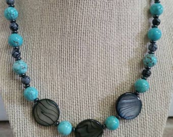 Eye-catching, 19 inch necklace and earrings set featuring shell disks, turquoise howlite, snowflake obsidian, bone hairpipe, and hematite